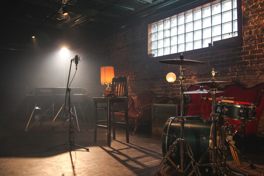 Empty room with drums, keyboard and microphone.