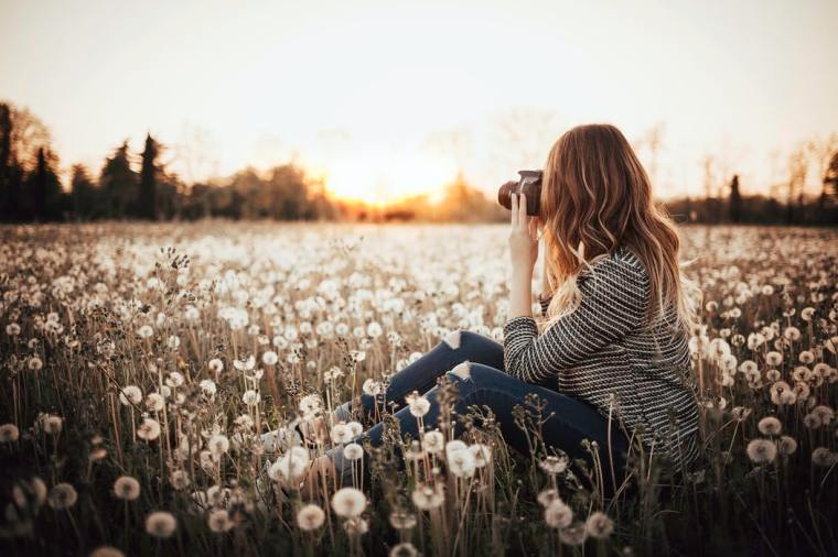 Female photographer sitting in a field of flowers.