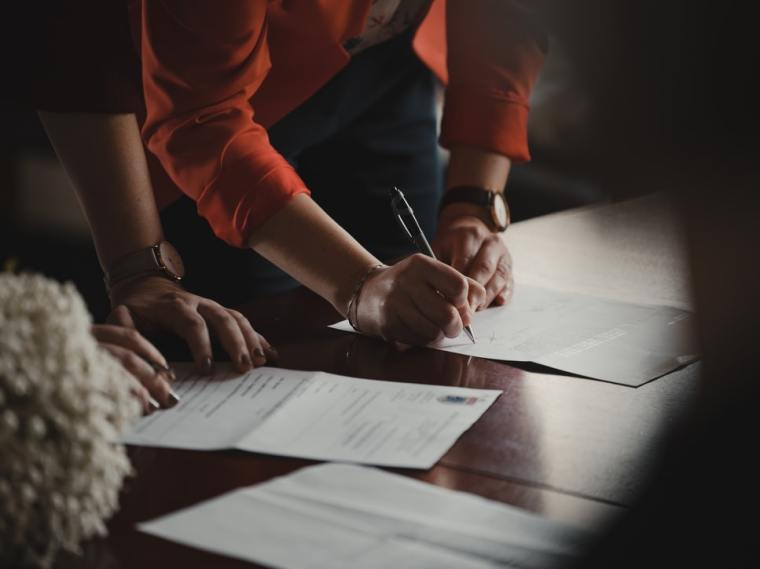 Two people signing a document.