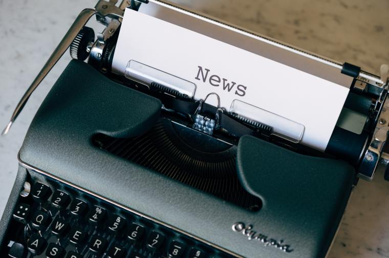 Olympia manual typewriter with a sheet of paper inserted reading 'news'.